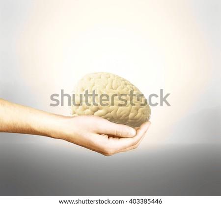 Male hand holding brain on light background - stock photo