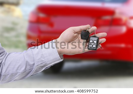 Male hand holding car keys against car background - stock photo