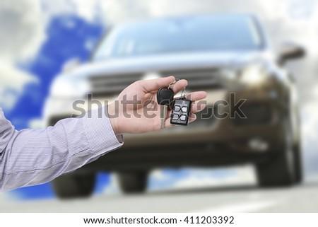 Male hand holding car keys against car background - stock photo