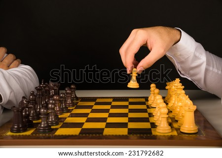 Male hand holding chess pawn, about to begin the game - stock photo