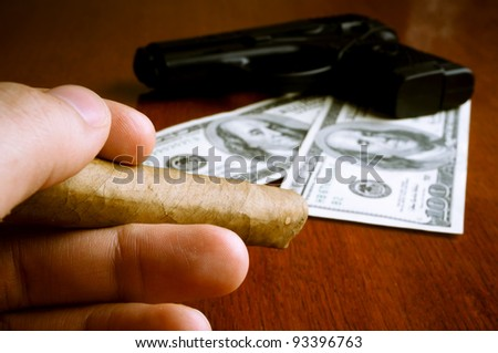 Male hand holding cigar with money and handgun in the background - stock photo