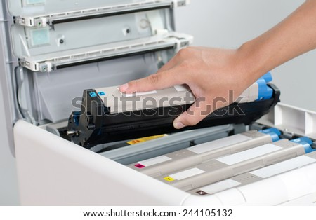 Male hand holding color printer toner