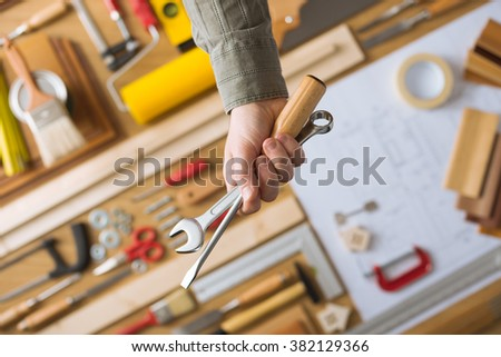 Male hand holding construction work tools, work table with build and repair tools top view, do it yourself and home renovation concept - stock photo
