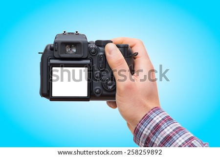 Male hand holding DSLR camera isolated on blue gradient background - In this photo the logos, brand, or anything that can bring to a particular object has been deleted to be 100% commercial. - stock photo