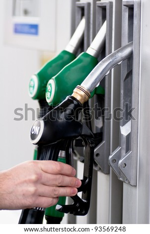 Male hand holding gasoline pump - stock photo