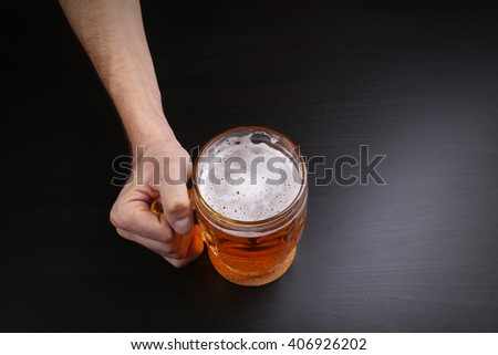 Male hand holding glass of beer on dark background - stock photo