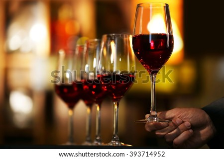 Male hand holding glasses of wine in the bar
