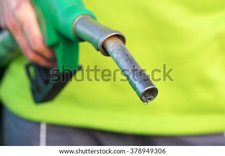 Male hand holding green pump - stock photo
