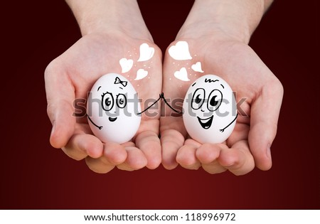 male hand holding holding eggs with smiley faces