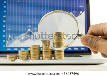 Male hand holding magnifying glass  with coin stacked and financial graph chart on laptop screen.For business growth and financial concept - stock photo