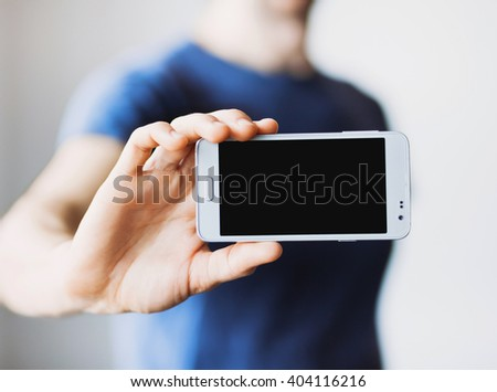 Male hand holding mobile smart phone with blank screen - stock photo