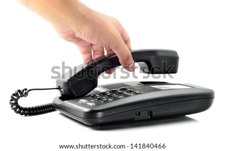 Male hand holding phone receiver over telephone - stock photo