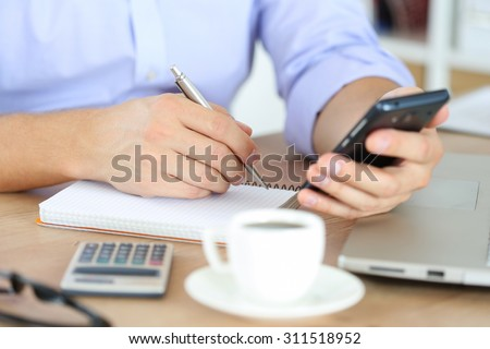 Male hand holding silver pen ready to make note in opened notebook while looking at cellphone. Businessman or employee at workplace writing business ideas, plans or tasks at personal organizer - stock photo