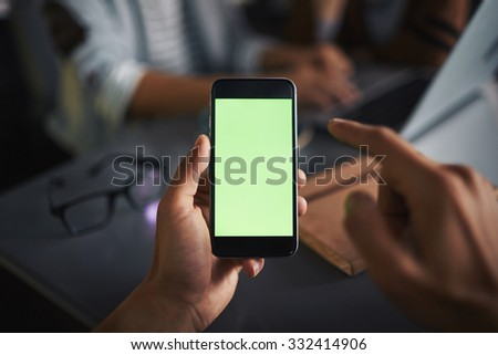 Male hand holding smartphone and being ready to touch screen - stock photo