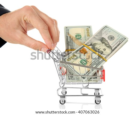 Male hand holding supermarket trolley with dollar banknotes, isolated on white