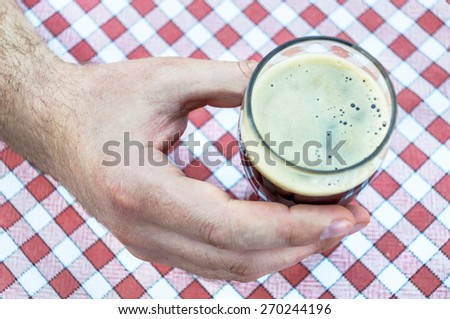 Male hand holding up a glass of dark beer on a tablecloth - stock photo