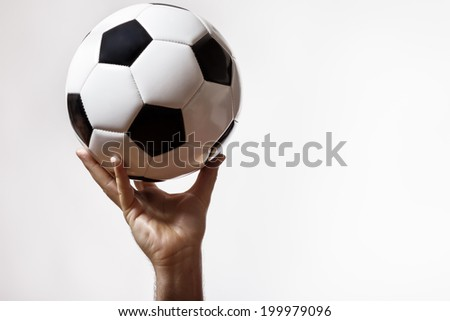 male hand holding up a traditional black and white football
