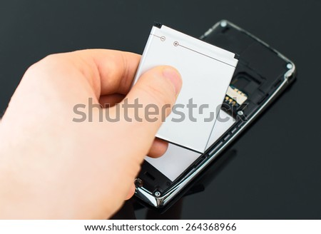 Male hand inserting battery to mobile phone. - stock photo