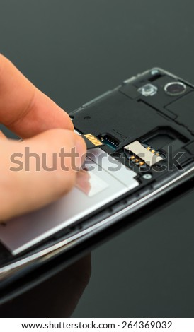 Male hand inserting Micro SD card to mobile phone. - stock photo