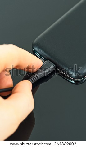 Male hand inserting micro USB to mobile phone. - stock photo