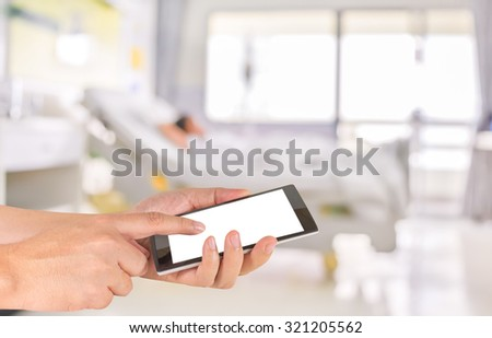 male hand is holding a modern touch screen phone and blurred image of Patient with drip in hospital for background usage. - stock photo