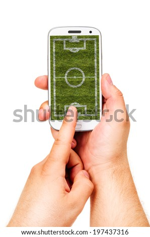 male hand is holding modern phone with soccer or football field on screen - stock photo