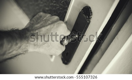Male hand is opening the door in black and white.