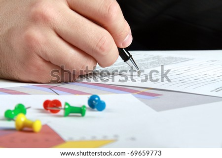 Male hand is writing in business document - stock photo
