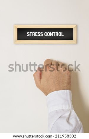 Male hand knocking on the door of Stress Control office. - stock photo