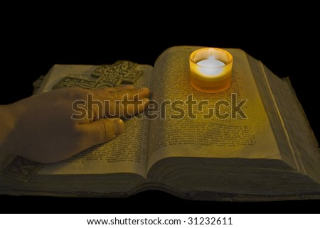 Male hand lies on ancient bible with a big christian cross - stock photo