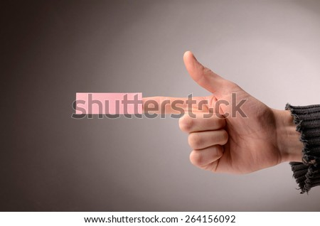Male hand making a pistol with a sticky note on the index finger - stock photo