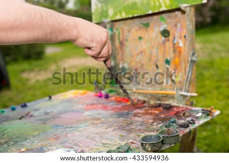 Male hand mixing dark colors of oils and acrylics paint with a paintbrush on an old multiclored palette on a sketchbook outside - stock photo