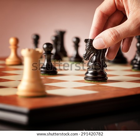 Male hand moving the black chess knight in focus in the middle of a chess game with blurred white rook in the foreground - stock photo