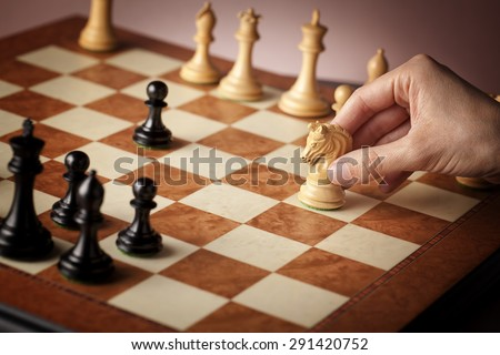 Male hand moving the white chess knight carved in natural boxwood in focus on luxury elm burl and bird's eye maple superior chessboard during the game of chess - stock photo