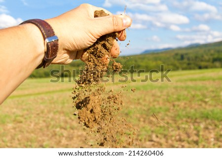 Male hand of a farmer with handful soil  - stock photo