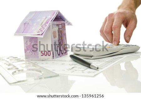 Male hand on a calculator calculating mortgage rates. - stock photo