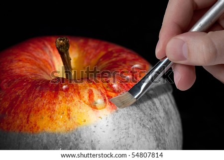 Male hand painting a fresh red wet apple which is partly black and white and partly colored - stock photo