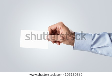 Male hand passing blank business card with copy space - stock photo