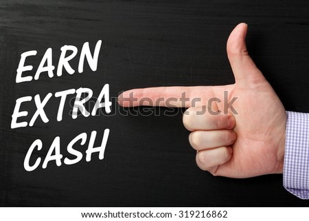Male hand pointing a finger at the phrase Earn Extra Cash in white text on a blackboard - stock photo