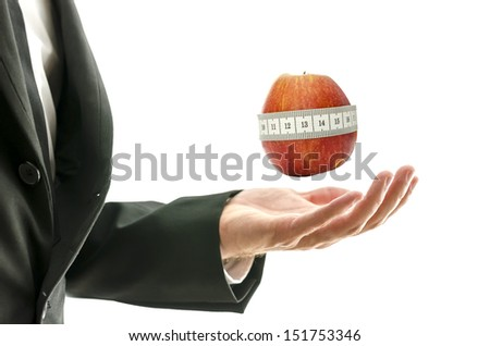 Male hand presenting apple wrapped with measuring tape.