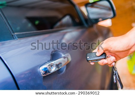 Male hand pressing on the remote control car alarm systems - stock photo