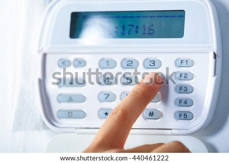 Male hand pressing the code on a house alarm - stock photo