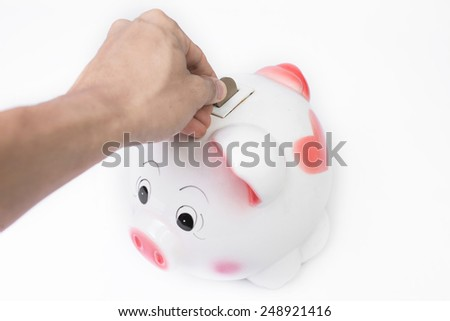 male hand putting a coin into piggy bank no white background. - stock photo