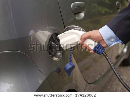 Male hand putting charger into an electric car.  Wearing shirt and suit. - stock photo