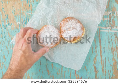 Male hand reaches and picking sweet sugary donut from rustic wooden kitchen table, classic hannukah sufganiyot or tasty bakery doughnuts overhead shot, top view - stock photo