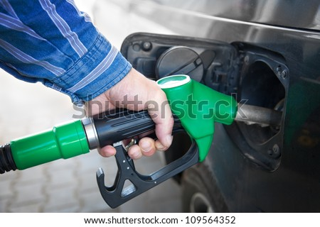 Male Hand Refilling the black Car with Fuel on a Filling Station - stock photo