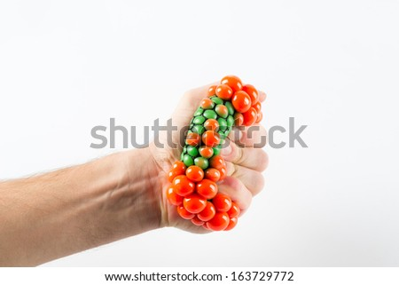 Male hand squeezing stress ball over plain background - stock photo