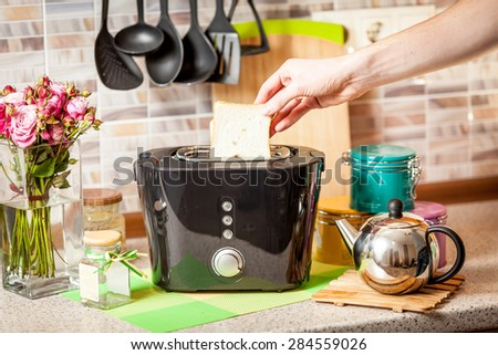 Male hand taking baked toast out of toaster - stock photo