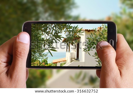 Male hand taking photo of Idyllic Greek house, villa, by the sea , between olive trees with cell, mobile phone. Greece holiday. - stock photo