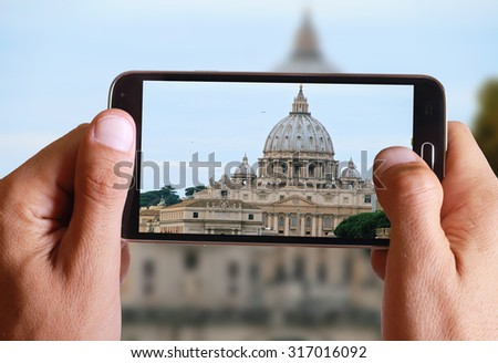 Male hand taking photo of st peter basilica and river Tiber from the bridge in Rome with cell, mobile phone. Europe travel, Italian holiday.